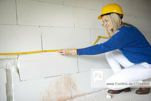 Female building contractor measuring wall with folding ruler while crouching at site