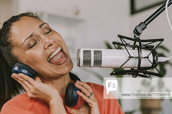 Female singer with headphones singing on microphone at home