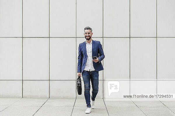 Smiling businessman with briefcase and mobile phone walking on footpath