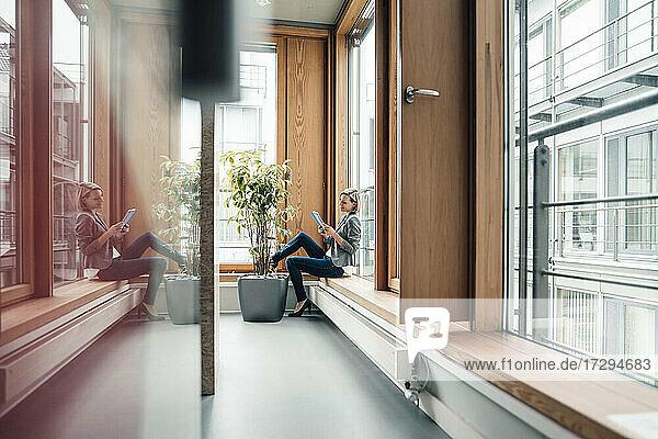 Geschäftsfrau  die ein digitales Tablet benutzt  während sie auf der Fensterbank sitzt