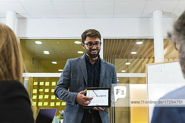 Smiling businessman explaining business strategy on digital tablet to male and female professionals in office