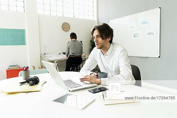Männlicher Unternehmer  der einen Laptop benutzt  während er mit einem Kollegen im Hintergrund im Büro sitzt