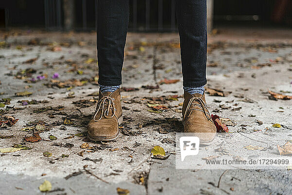Young man wearing shoes standing on footpath