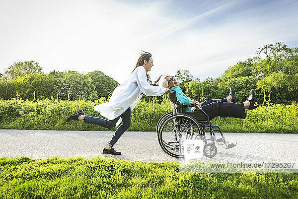 Senior woman in wheelchair enjoying with caretaker in park