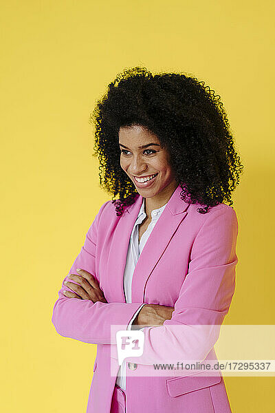 Smiling female professional with arms crossed looking away