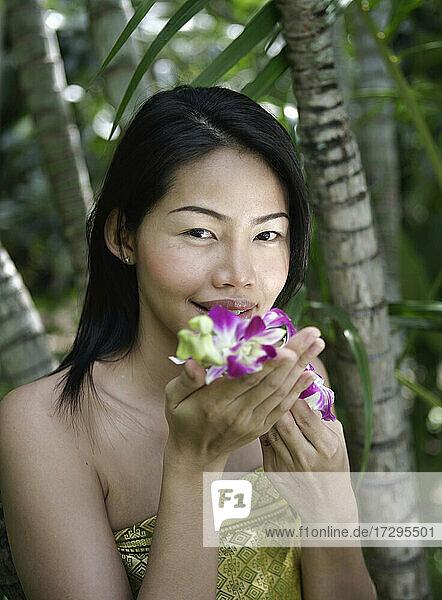 Thailand  Insel Koh Samui  Porträt einer lächelnden Frau  die an Orchideen riecht