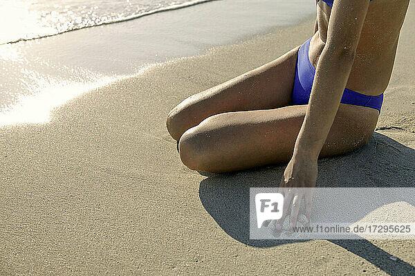 Frau im Bikini sitzend am Strand  tiefer Ausschnitt