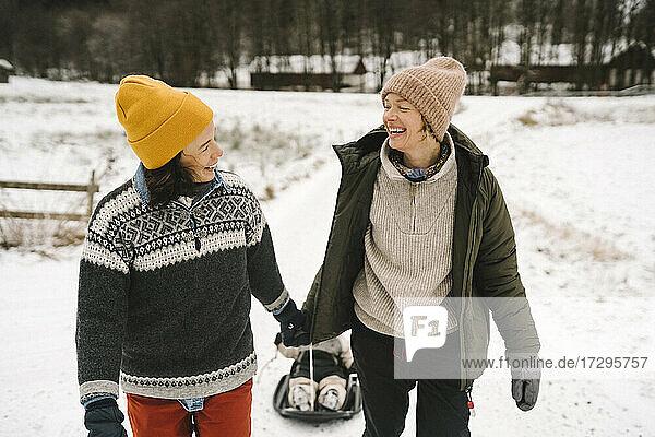 Lächelndes lesbisches Paar schaut sich gegenseitig an  während es seine Tochter durch den Schnee zieht