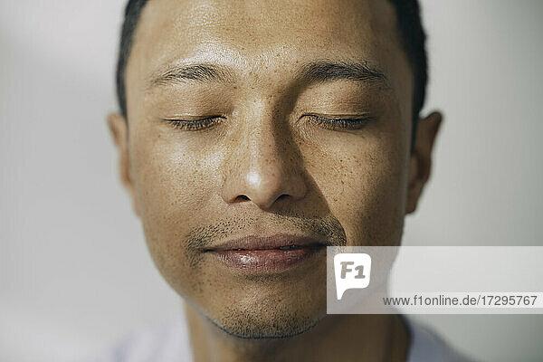 Lächelnder Mann mit geschlossenen Augen gegen weiße Wand