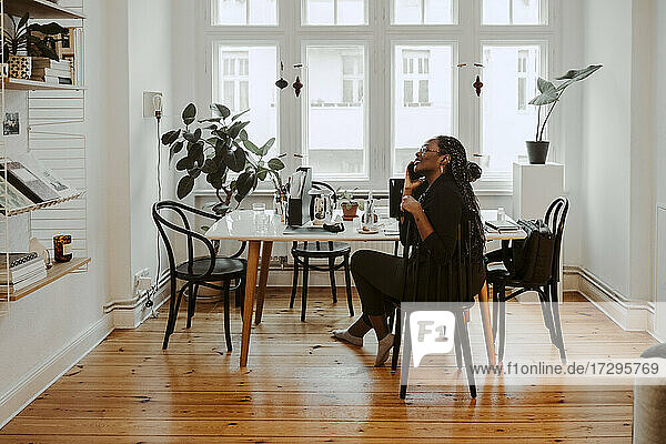 Junge weibliche professionelle Gespräch am Handy sitzen im Home-Office