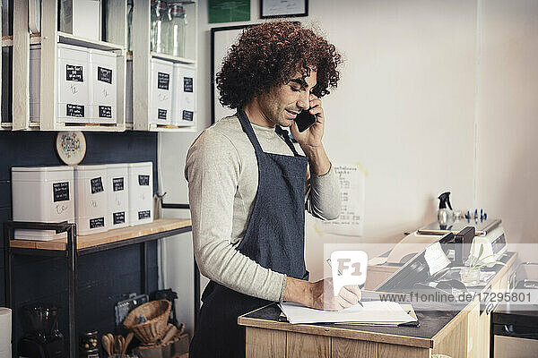Salesman talking on mobile phone while writing at checkout counter