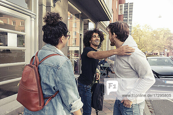 Happy male friends greeting each other while standing by young woman outside cafe