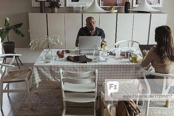 Geschäftsmann im Gespräch mit weiblicher Kollegin bei gleichzeitiger sozialer Distanzierung im Home Office