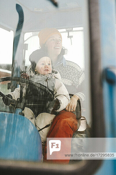 Mother and daughter sitting in tractor seen through windshield