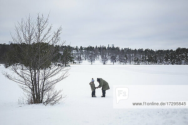 Woman helping daughter with jacket while standing on snow during winter