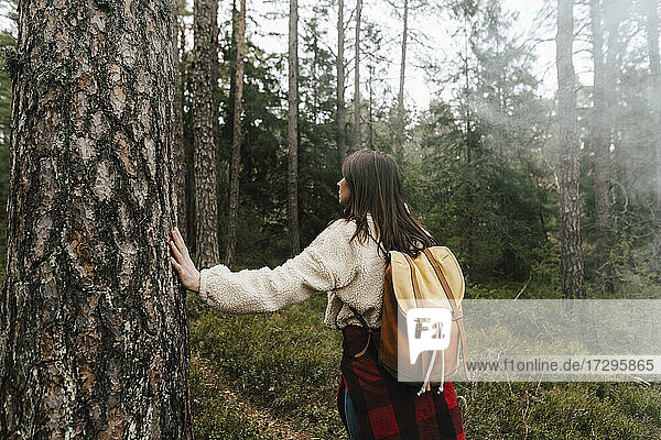 Rear view of female explorer walking in forest
