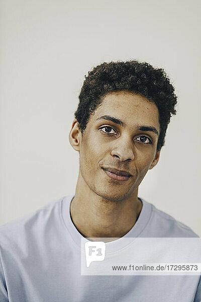 Lächelnder junger Mann vor weißem Hintergrund