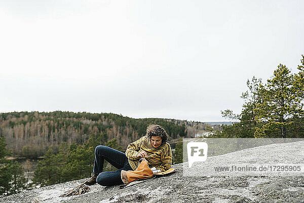 Female hiker peeking in backpack while lying on mountain against clear sky