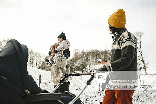 Lächelnde Frau  die ihre Tochter auf der Schulter trägt  während ihre Freundin im Winter mit dem Wagen spazieren geht