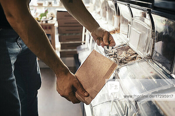 Midsection of male customer filling slice coconut in paper bag at organic store