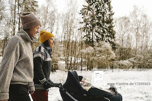 Reife Frau schiebt Baby-Kinderwagen beim Spaziergang mit Freundin im Winter
