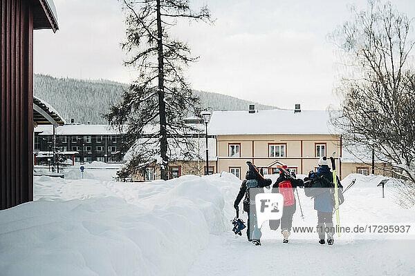 Volle Länge Rückansicht von Freunden tragen Rucksack beim Gehen auf Schnee im Skigebiet