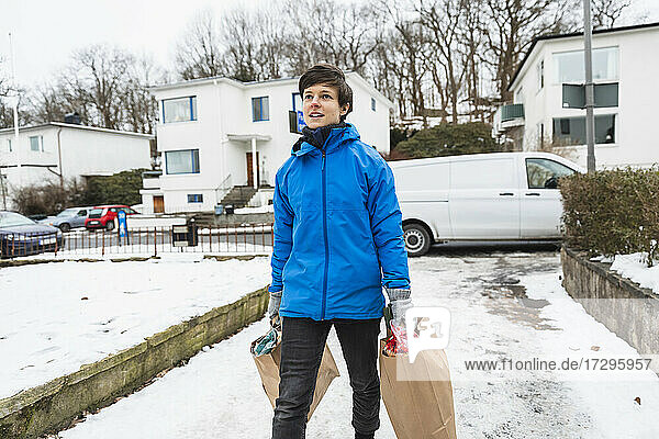 Junge Liefer Frau zu Fuß  während das Tragen Papiertüten im Winter