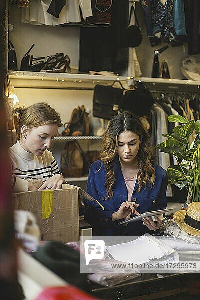 Weibliche Besitzerin macht Notizen auf einem digitalen Tablet  das neben einem Kollegen in einem Bekleidungsgeschäft steht