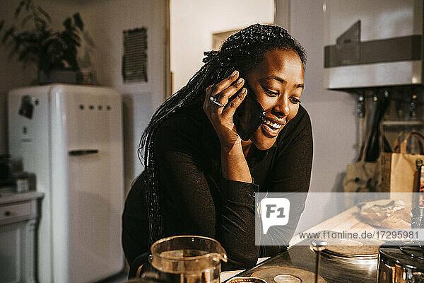 Junge Frau spricht durch Smartphone  während lehnt sich auf Küchentheke