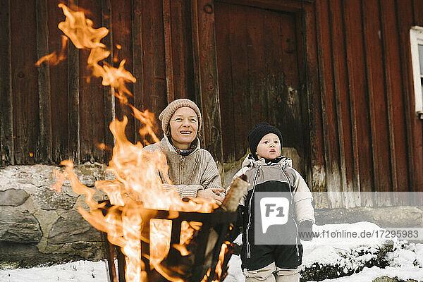 Mutter mit Tochter in der Nähe von brennenden Feuergrube wegschauen