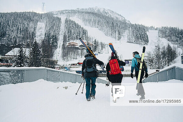 Rear view of female and male friends walking on snow at ski resort during vacation