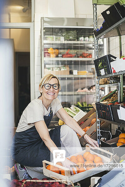 Portrait of smiling female owner arranging fruits in rack at store