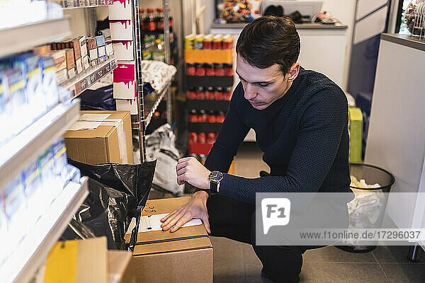 Male entrepreneur analyzing box while working in store