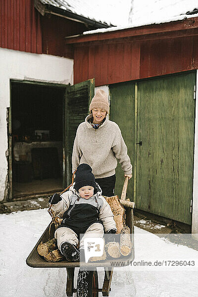 Smiling mother carrying daughter sitting on firewood in wheelbarrow during winter
