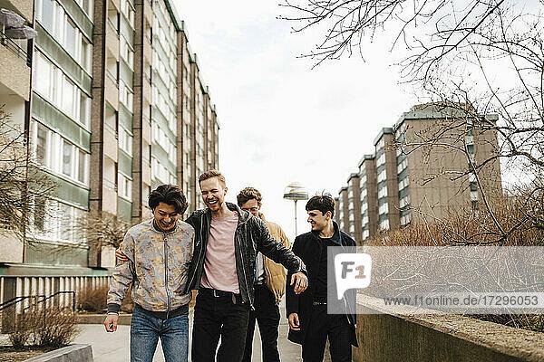 Fröhlich männliche Freunde zu Fuß durch Gebäude in der Stadt