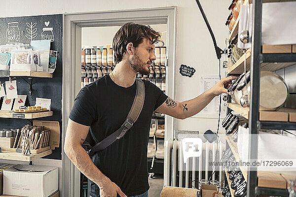 Male customer looking at jar on rack in organic shop