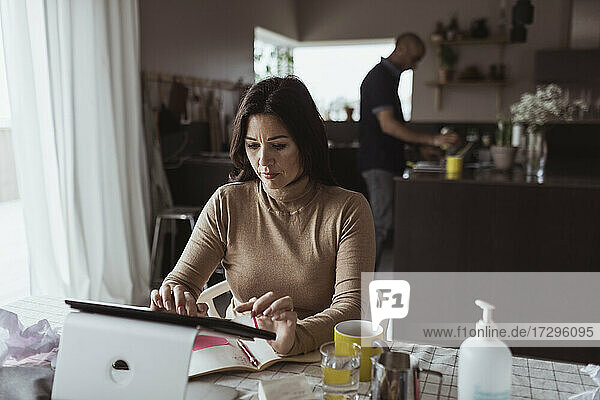 Female entrepreneur working on digital tablet at home