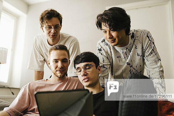 Männliche Freunde teilen sich ein digitales Tablet im Wohnzimmer