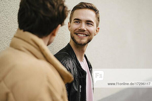 Lächelnder Mann im Gespräch mit männlichem Freund gegen die Wand