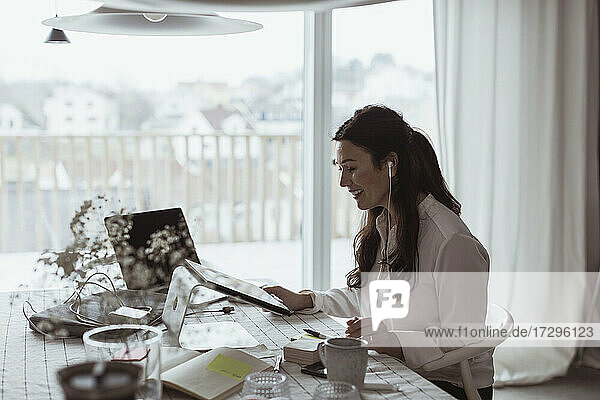 Smiling businesswoman using digital tablet at home office