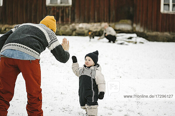 Rear view of mother giving high-five to daughter during winter