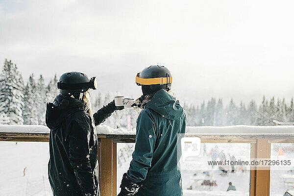 Weibliche Freunde toasting Kaffeetassen während stehend durch Geländer im Winter