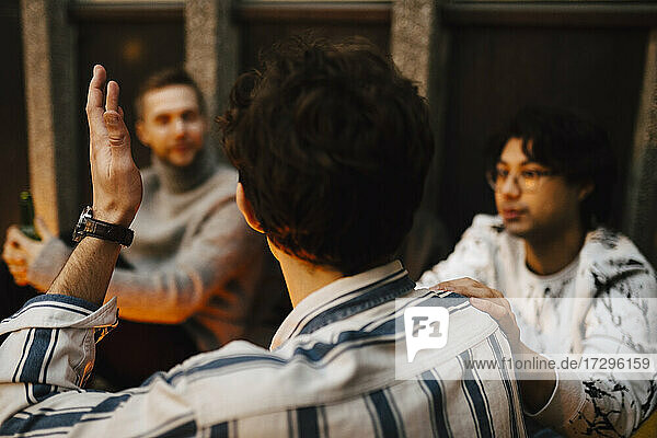 Rear view of man gesturing while talking with friends at balcony