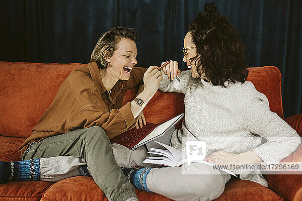 Cheerful lesbian couple sitting together on sofa at home