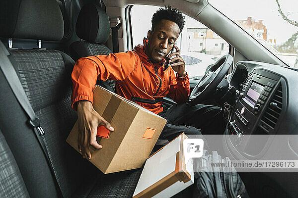 Männlicher Fahrer  der am Telefon spricht  während er mit Paketen im Lieferwagen sitzt