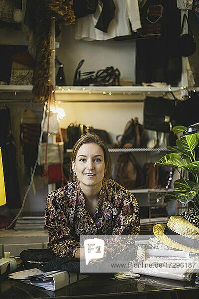 Porträt einer Besitzerin  die sich in einem Bekleidungsgeschäft an einen Tisch lehnt