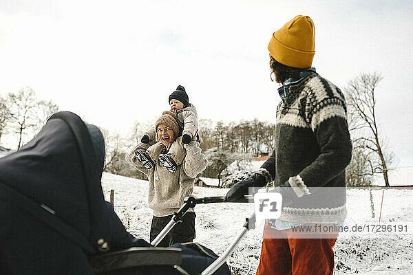 Fröhliche Frau trägt Tochter auf der Schulter beim Spaziergang mit Freundin im Winter