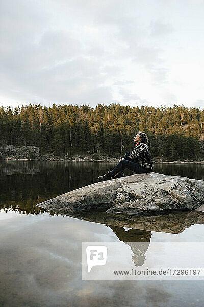 Female hiker sitting on rock by lake against sky
