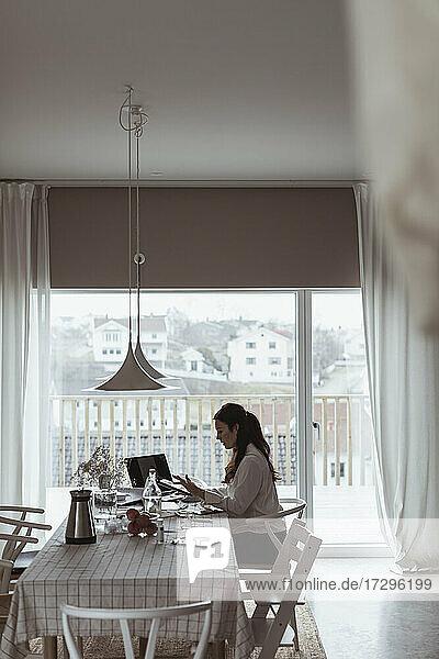 Geschäftsfrau arbeitet am Laptop im Büro zu Hause