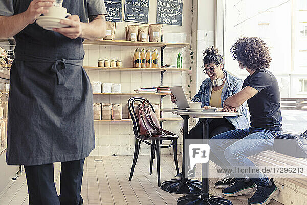 Happy female and female friends discussing over laptop at cafe